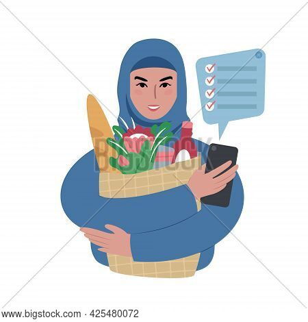 Young Woman Wearing A Headscarf With Groceries Bag And A Shopping List On A Smartphone.