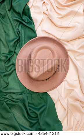 A Fedora Hat Made Of Felt, On Scarves Green-beige Fabric Draped With Soft Folds