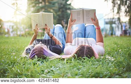Teenagers Reading Books Together In A University Campus While Lying In Grass - Millennials Learning