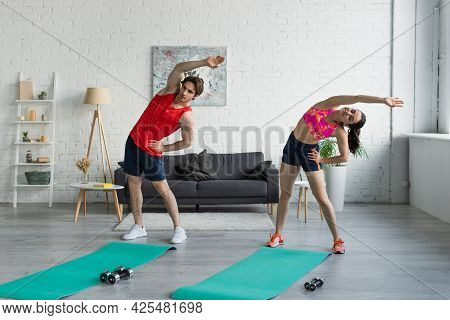 Fit Young Couple In Sportswear Doing Exercise Near Fitness Mats Before Workout At Home