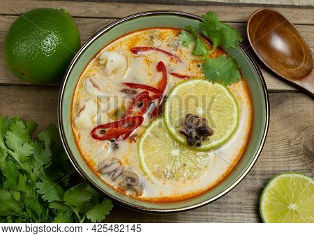 Top View Of Tom Yam Soup With Lime Slices, Seafood And Chili Peppers In A Green Bowl On A Wooden Rus