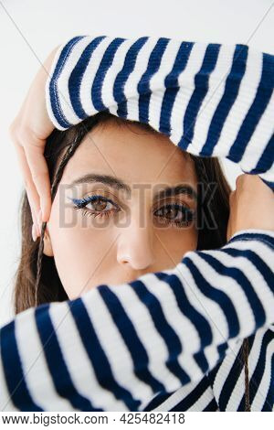 Stylish Armenian Woman In Striped Pullover Looking At Camera Isolated On White