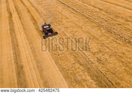 Aerial View Of Wheat Harvest. Drone Shot Flying Over Combine Harvesters Working On Wheat Field. Harv