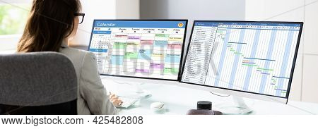 Woman Using Electronic Calendar And Scheduling Agenda On Screen