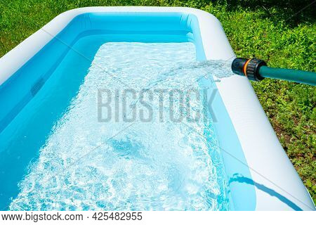 Filling The Inflatable Pool With Water. Swimming Pool In The Summer Garden. Side View, Horizontal.