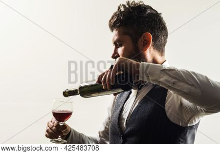Bearded Man With Bottle And Glass Of Wine. Sommelier Tasting Wine In Restaurant. Alcohol Tasting.