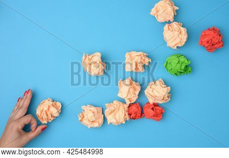 Hand Hold Crumpled Sheets Of Colored Paper On A Blue Background. Solution Concept, Brainstorming, Op