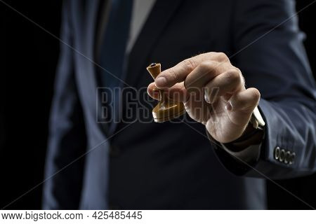 Business Planning Strategy And Concept. A Businessman In A Dark Suit Holds A White Chess Queen In Hi