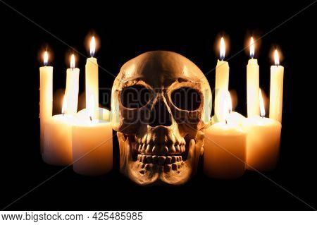 Human Skull Among Burning Candles In The Darkness, Scary Still Life, Altar.