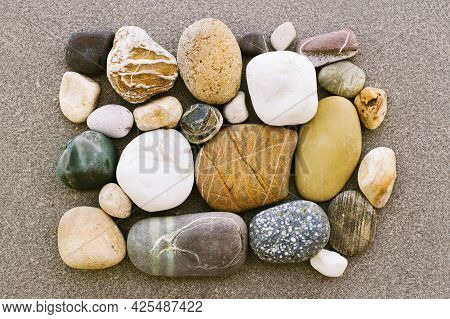 Multicolored Stones Of Warm Shades And Sizes Are Neatly Laid Out, Top View