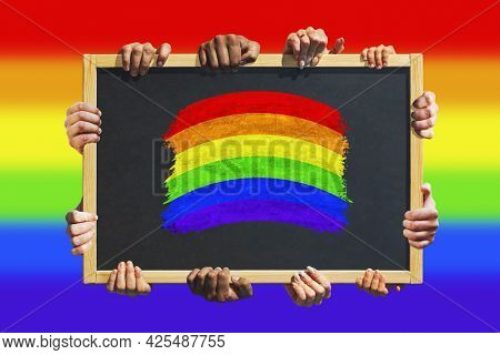 A Lot Of Hands Are Holding A Poster With Lgbt Flag - Symbol Of Love And Tolerance. Lesbian, Gay, Bis