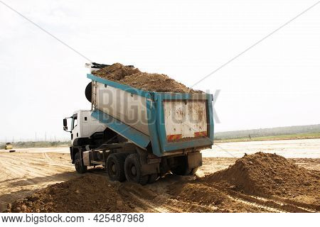 Dump Truck Unloads Clay Soil For The Construction Of A New Highway. Clay For Laying The Foundation O