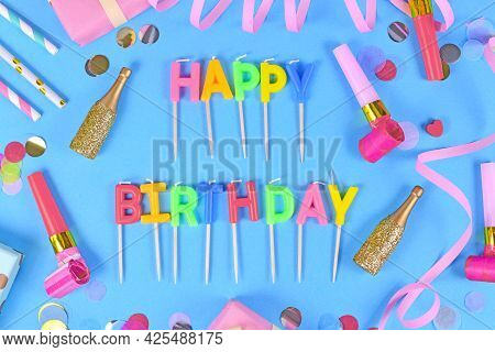Party Flat Lay With Happy Birthday Candles, Confetti And Paper Streamers On Blue Background