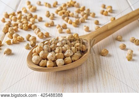 Dry Chickpea Beans In A Large Wooden Spoon On A White Wooden Table. Raw Ingredient For Hummus And He