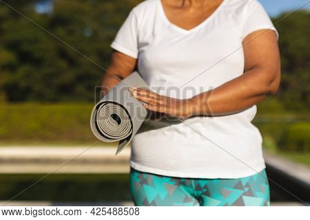 Midsection of senior african american woman with yoga mat by outdoor pool in countryside. retirement and active senior lifestyle concept.