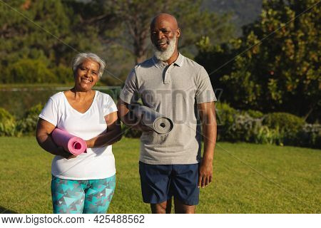 Portrait of smiling senior african american couple with yoga mat in countryside retreat. retirement and active senior lifestyle concept.