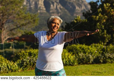 Senior smiling african american woman practicing yoga in stunning countryside. retirement and active senior lifestyle concept.