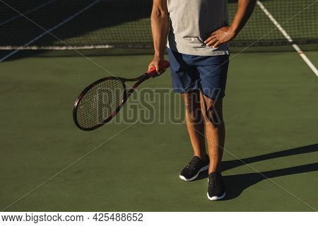 Midsection of senior african american man holding tennis racket on tennis court. retirement and active senior lifestyle concept.