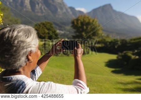 Senior african american woman taking photographs on smartphone of stunning view in sunny garden. retreat, retirement and happy senior lifestyle concept.