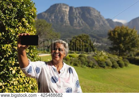 Senior african american woman taking selfies with smartphone in sunny garden. retreat, retirement and happy senior lifestyle concept.