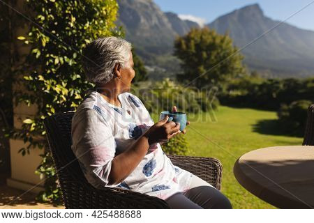 Senior african american woman having tea in sunny garden stunning countryside. retreat, retirement and happy senior lifestyle concept.