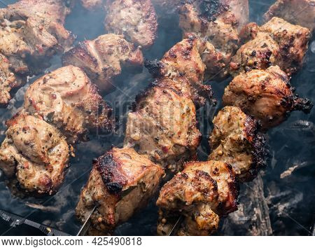 Different Kinds Of Meat On Metal Skewers - Pork And Chicken Grilling On Fire, Coals And Smoke In Gri