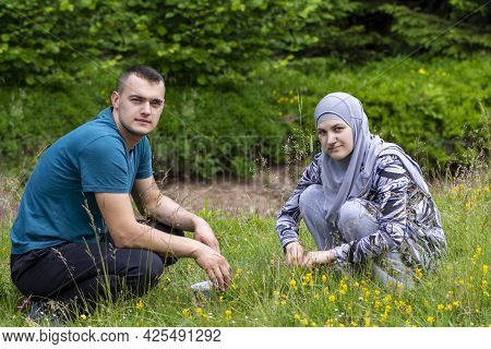 Young Muslim Couple Squatting On Grass And Looking To The Camera With Different Face Expressions. Lo