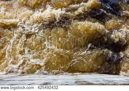 Foamy Stream Of Water Beats Against The Concrete Wall Of The Dam