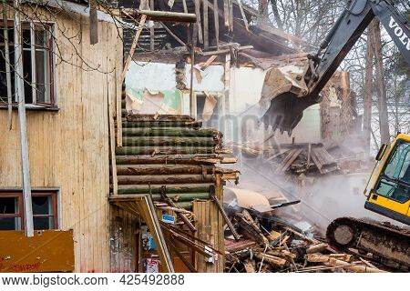 Demolition Of An Old Wooden Log House With A Volvo Excavator: Kaluzhskiy Region, Russia - April 2021