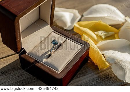 Beautiful Ring With A Blue Diamond Set In A Brown Proposal Box With White And Yellow Petals On One S