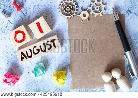 August 1. Date Of August Month. Number Cube With A Flower And Notebook On Diamond Wood Table For The