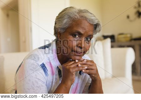 Portrait of senior african american woman sitting on sofa looking at camera. retreat, retirement and senior lifestyle concept.
