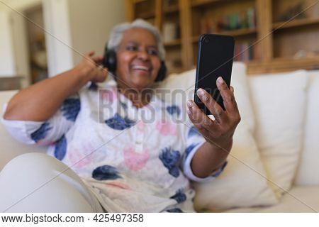 Senior african american woman sitting on sofa wearing headphones using smartphone. retreat, retirement and happy senior lifestyle concept.
