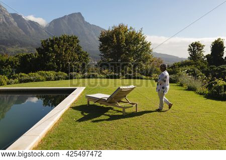 Senior african american woman walking to deckchair by swimming pool in sunny stunning countryside. retreat, retirement and happy senior lifestyle concept.