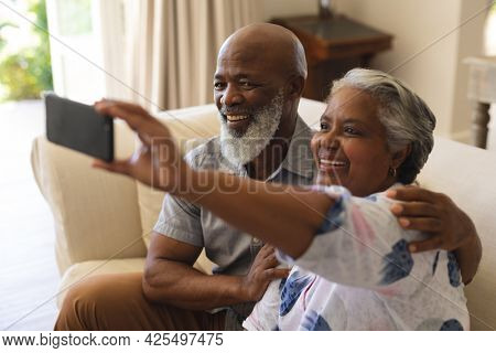 Senior african american couple sitting on sofa using smartphone taking selfies. retreat, retirement and happy senior lifestyle concept.