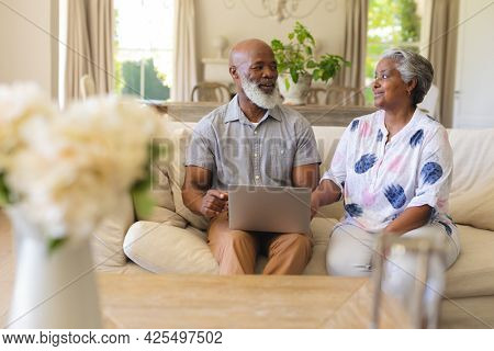Senior african american couple sitting on sofa using laptop and smiling. retreat, retirement and happy senior lifestyle concept.