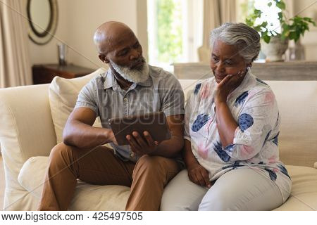 Senior african american couple sitting on sofa using tablet. retreat, retirement and happy senior lifestyle concept.
