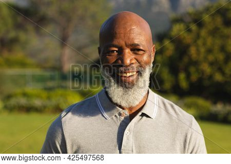 Portrait of smiling senior african american man in stunning countryside. retirement and active senior lifestyle concept.