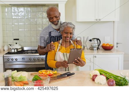 Senior african american couple cooking together in kitchen using tablet. retreat, retirement and happy senior lifestyle concept.