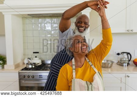 Senior african american couple dancing together in kitchen smiling. retreat, retirement and happy senior lifestyle concept.