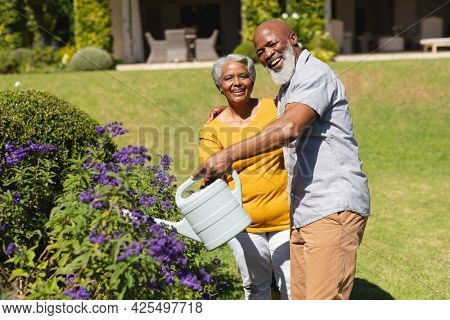 Portrait of senior african american couple spending time in sunny garden together watering flowers. retreat, retirement and happy senior lifestyle concept.