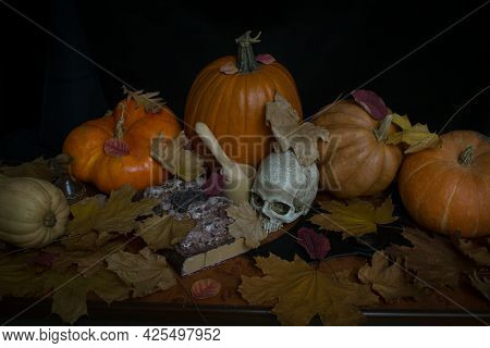 Pumpkins, Witch Hat, Spell Book And Skull On A Table. Halloween Eve Concept.