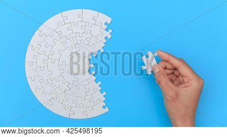 White Jigsaw Puzzle On A Blue Background. Completing Final Task, Missing Jigsaw Puzzle Pieces And Bu