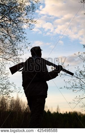 A Black Silhouette Of A Hunter With An Unloaded Shotgun On His Shoulder Against The Background Of Th