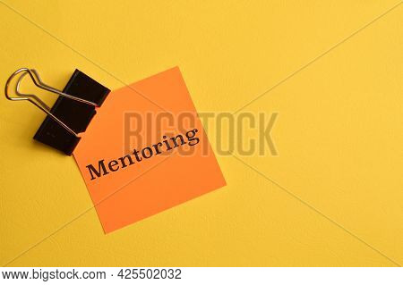 Orange Paper Written With Text Mentoring Isolated On Yellow Background