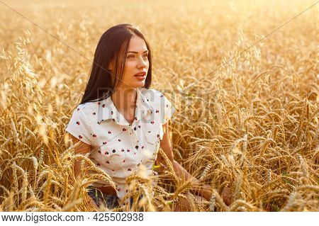 Beauty Girl Outdoors Enjoying Nature On Wheat Field. Beautiful Model Girl With Long Hair On Golden F