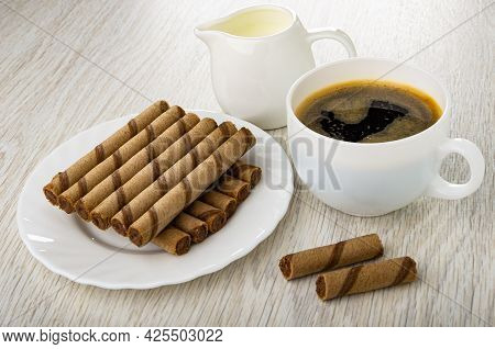 Pitcher With Milk, Brown Striped Wafer Rolls With Chocolate Filling In White Plate, Black Coffee In