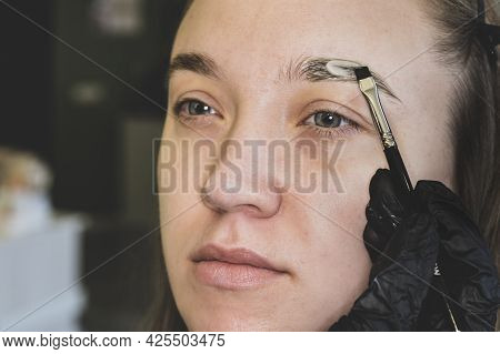 Eyebrow Coloring Is A Cosmetic Procedure. Close Up Of Esthetician Filling In Eyebrows Of Female Clie