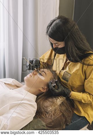 A Girl In A Beauty Salon On The Procedure Of Coloring Her Eyelashes. Care For Eyebrows And Eyelashes