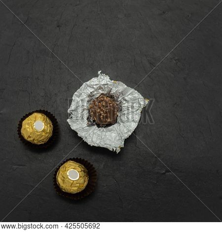 Chocolate-nut Sweets On The Background Of A Black Stone Tile. Two Candies Are Wrapped In Golden Foil